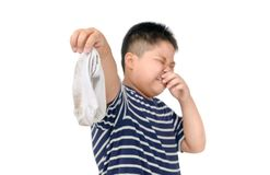 Fat boy holding dirty stinky socks isolated. On white background, unpleasant smell concept royalty free stock photos