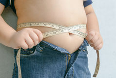 Fat boy measuring his belly Royalty Free Stock Image
