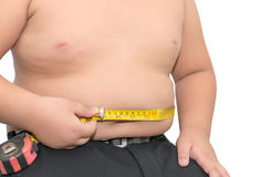Fat boy measuring his belly with measurement tape isolated Royalty Free Stock Images