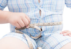 Fat boy measuring his belly with measurement tape isolated Royalty Free Stock Image