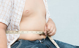 Fat boy measuring his obese. On gray background Royalty Free Stock Image