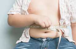 Fat boy measuring his obese. On gray background Stock Photo