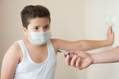 Fat boy in the medical mask looks at hand with a syringe Royalty Free Stock Photography