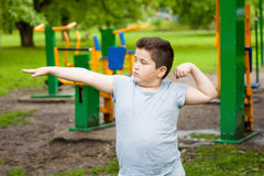 Fat boy shows his muscles in background of exercise equipment Stock Image