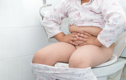 Fat boy sitting on the toilet. Royalty Free Stock Images