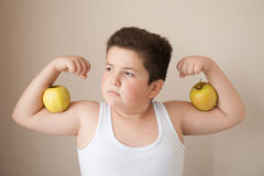 Fat boy in t-shirt shows muscles with apples on his biceps Stock Photo