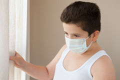 Fat boy wearing shirt and surgical mask looking out the window Royalty Free Stock Images