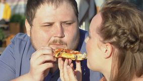 Fat boyfriend and girlfriend eating pizza outdoors romantic date, junk food diet. Stock footage stock video footage