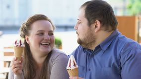 Fat boyfriend and girlfriend enjoying ice-cream dessert, overeating sweets. Stock footage stock video