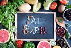 Fat burn. On a chalkboard surrounded by fresh detox food ingredients royalty free stock images