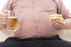 Fat business man holding beer mug and hamburger. On a sofa Royalty Free Stock Photography
