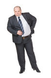 Fat businessman glowering at the camera. Fat overweight businessman in a stylish suit standing with his hand on his hip glowering at the camera with a displeased Royalty Free Stock Photo