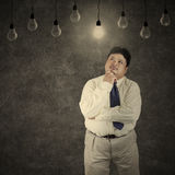 Fat businessman looking at bright lightbulb Royalty Free Stock Photos