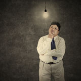Fat businessman looking at bright lightbulb 1 Royalty Free Stock Photography
