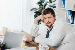 fat businessman sitting at workplace with crumpled papers royalty free stock photo