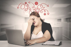 Fat businesswoman having messy thought. While working with laptop computer in the office Stock Photo
