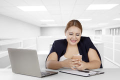 Fat businesswoman with smartphone in office Stock Photo