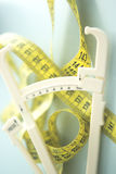 Fat caliper measuring tape. Fat caliper and measuring tape used to measure waistline, bodyfat levels for fitness and obesity checks Royalty Free Stock Image