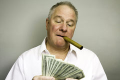 Fat Cat. Man with cigar in mouth admiring one hundred dollar bills Royalty Free Stock Photos