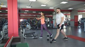 Fat caucasian man with a beard in the gym performs an exercise squats with dumbbells under the supervision of a
