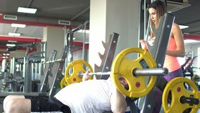 Fat caucasian man with a beard performs a dumbbell bench press exercise on his back while securing a beautiful girl
