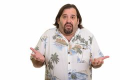 Fat Caucasian man looking confused with both arms raised. Isolated against white background royalty free stock image