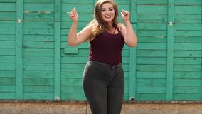 A fat cheerful girl jumps and shows her thumb up against the green wall. A fat cheerful girl jumps and shows her thumb up against the green wall in the Park in stock footage