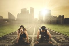 Fat couple ready to compete. Image of young fat couple ready to compete while kneeling on the road with numbers 2018 Stock Image