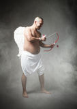 Fat Cupid with bow and arrow on hand Stock Photography