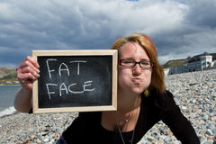 Fat face. A pretty young woman pulls a joking fat face while holding up a sign with 'fat face ' written on it Stock Images