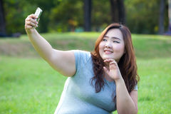 Fat female takes travel selfie at the park Royalty Free Stock Photography