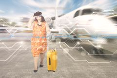 Woman with virtual reality headset in the airport. Fat female tourist using virtual reality headset while standing with a suitcase in the airport Stock Photos
