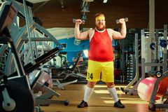 Fat funny man in the gym. Fat funny man in the gym doing exercises with dumbbells Royalty Free Stock Photos