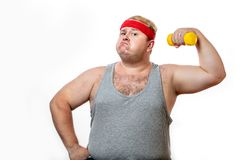 Fat funny man in red headband shows his muscles with dummbell and emotions royalty free stock photo