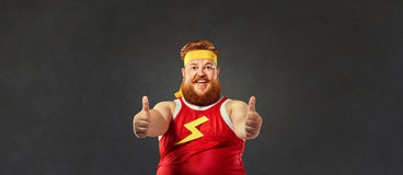 Fat funny man in sportswear keeps his fingers up. Thick fat funny man in sportswear keeps his fingers up Royalty Free Stock Image