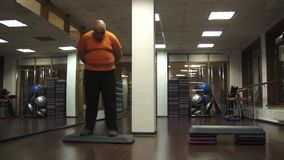 Fat funny man is standing on a step in a fitness room with a confused look. Camera moving from right into left stock footage