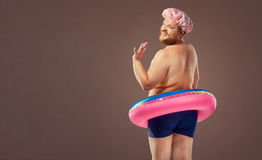 Fat funny man in a swimsuit with an inflatable circle. Stock Photography