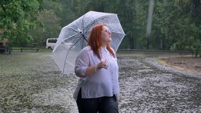 Fat ginger girl with glasses is walking in park under rain, watching up, holding umbrella
