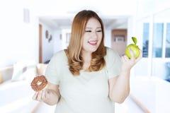Fat girl choosing apple or donut Stock Image