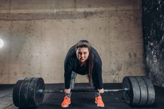 Fat girl exercises with big barbell for losing her weight royalty free stock photography