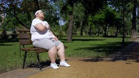 Fat girl exhausted after jogging takes minute rest on bench, combating obesity royalty free stock images