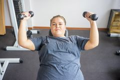 Fat girl in a gym. A portrait of a fat girl exercising in a gym royalty free stock photography