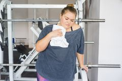 Fat girl in a gym. A portrait of a fat girl exercising in a gym royalty free stock photos