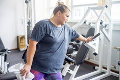 Fat girl in a gym. A portrait of a fat girl exercising in a gym royalty free stock photo