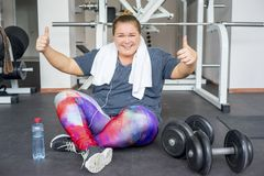 Fat girl in a gym royalty free stock photography
