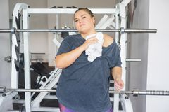 Fat girl in a gym. A portrait of a fat girl exercising in a gym royalty free stock images