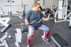 Fat girl in a gym. A portrait of a fat girl exercising in a gym stock photos