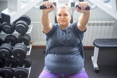 Fat girl in a gym. A portrait of a fat girl exercising in a gym stock photography