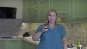 Fat girl in the kitchen. Fat girl drinks from a bowl and looks at a jar of legacy stock video