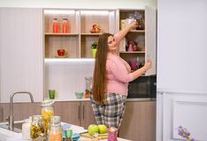 Fat girl in the kitchen. Pulls out of the closet dishes stock photo